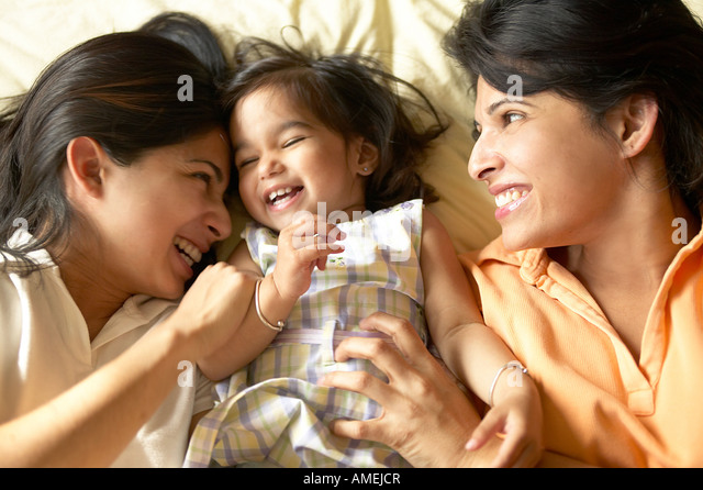 Two Women and Baby Laying on Bed - Stock-Bilder