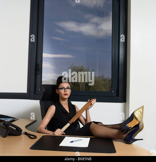 Businesswoman holding a cricket bat - Stock Image