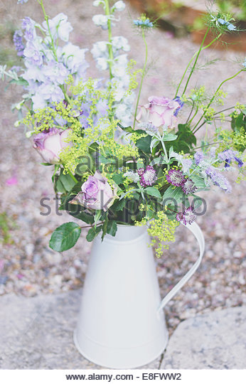 Purple flower arrangement in vintage milk jug - Stock Image