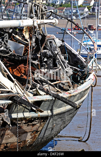 Charred Wreckage of a burnt out boat moored in the estuary of the River Conwy in North Wales. - Stock Image