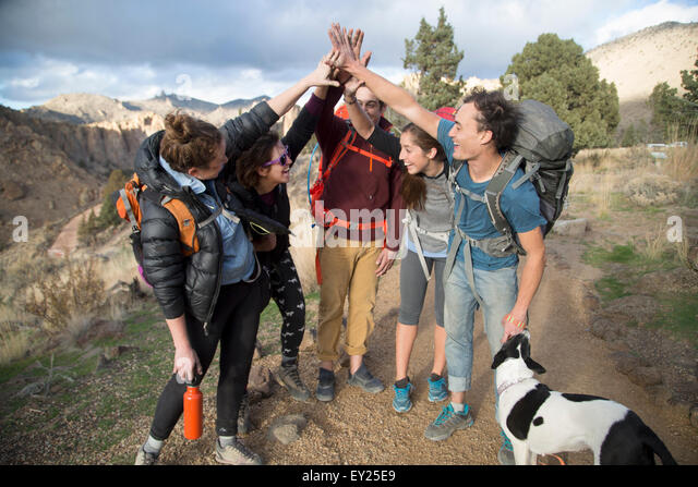 Hikers doing high five, Smith Rock State Park, Oregon, US - Stock Image