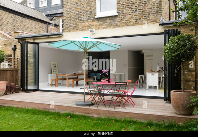 Decked patio with parasol of London Victorian townhouse with modern extension - Stock Image