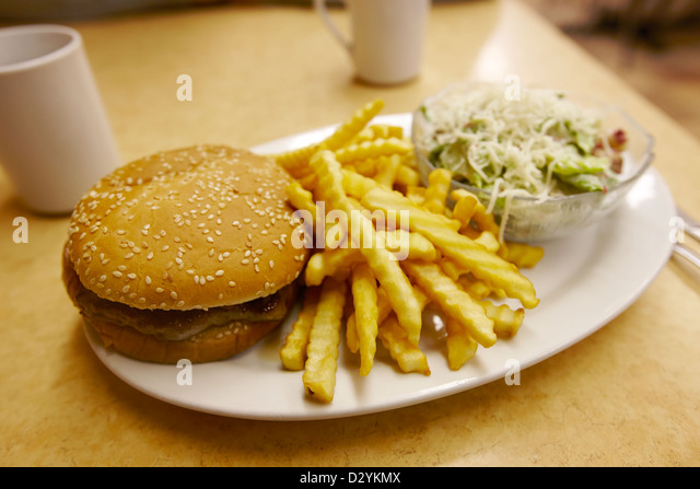 burger crinkle cut fries and salad in a cheap diner in north america - Stock Image