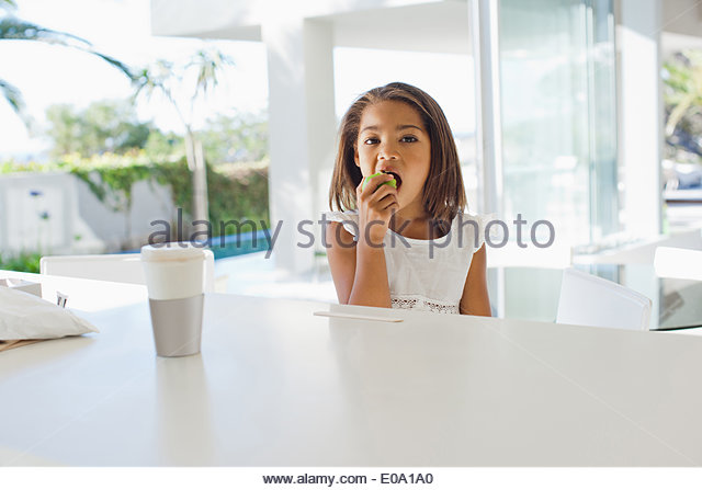 Smiling girl eating green apple - Stock Image