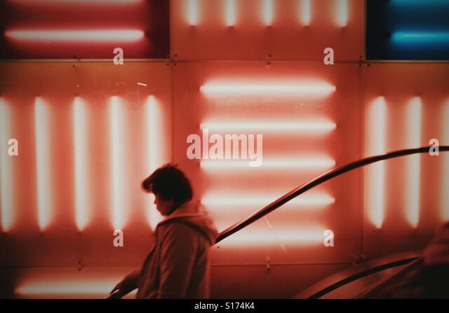 Woman riding an escalator in front of red neon lights - Stock-Bilder