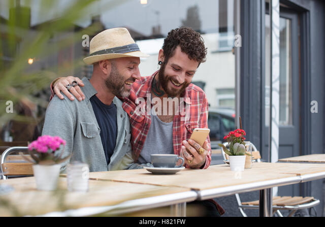 Gay couple sat sharing phone in cafe - Stock-Bilder
