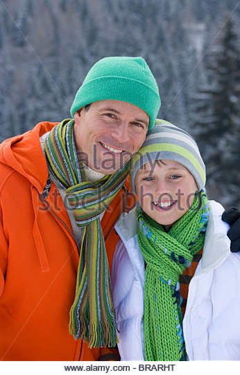 Father and son in cap and scarf smiling together outdoors - Stock Image