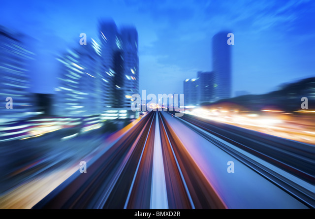 High speed train passing in between Kuala Lumpur City during dusk hour. Focus on the rail road. - Stock Image