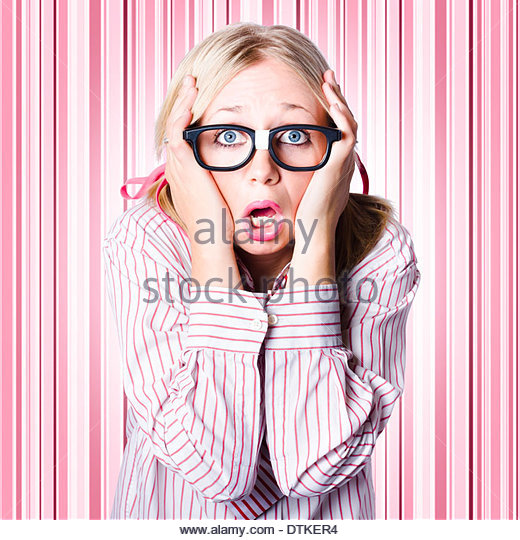 Dorky woman wearing spectacles clutching head with look of panic when making a difficult business decision - Stock Image