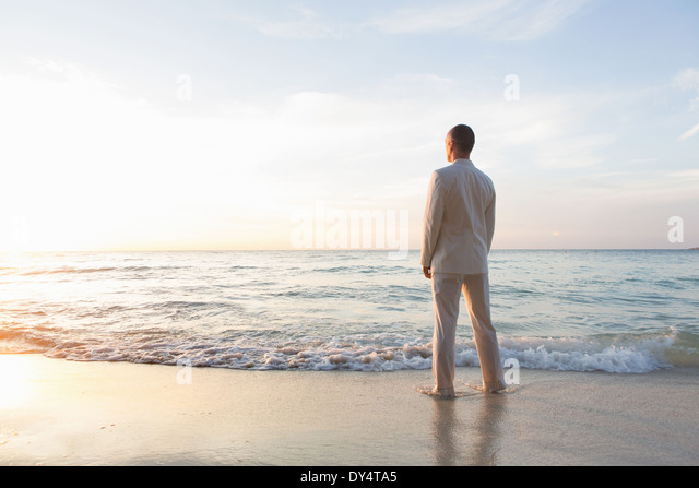 Businessperson standing in sea, rear view - Stock Image