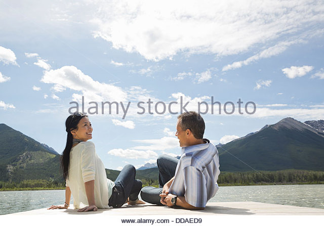 Mature couple relaxing on dock - Stock Image