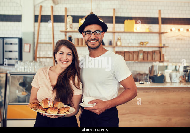 Portrait of happy young man and woman with food and cafe at coffee shop. Couple having food in a restaurant. - Stock-Bilder