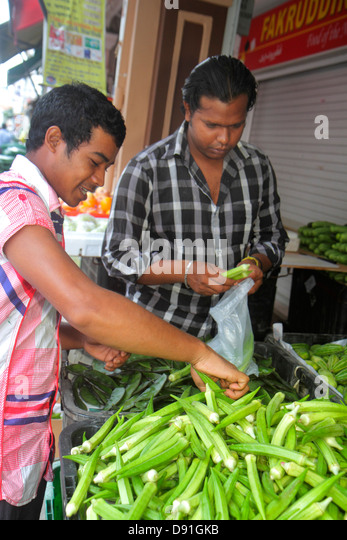 Singapore Little India Asian man produce vendor market okra - Stock Image