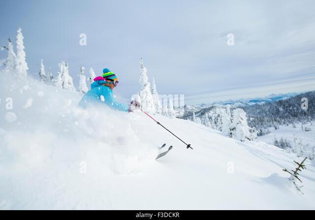 Mature woman speeding on ski slope - Stock Image