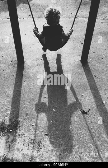 Boy on swing with long shadows - Stock Image