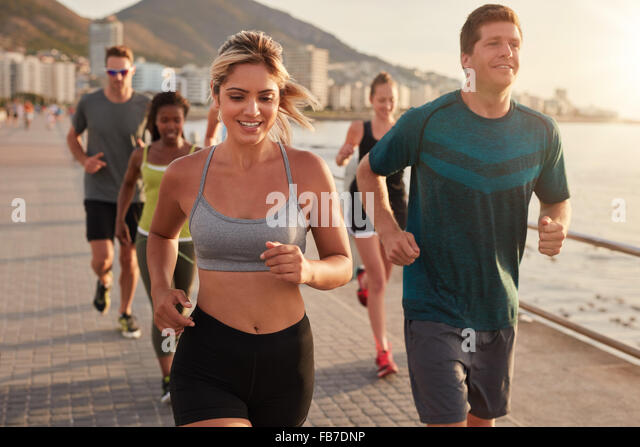 Portrait of fit young woman running with friends on street along the sea. Running club group training outdoors. - Stock Image