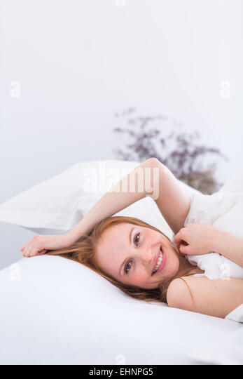 Woman laying in bed, head on pillow, smiling at camera - Stock-Bilder