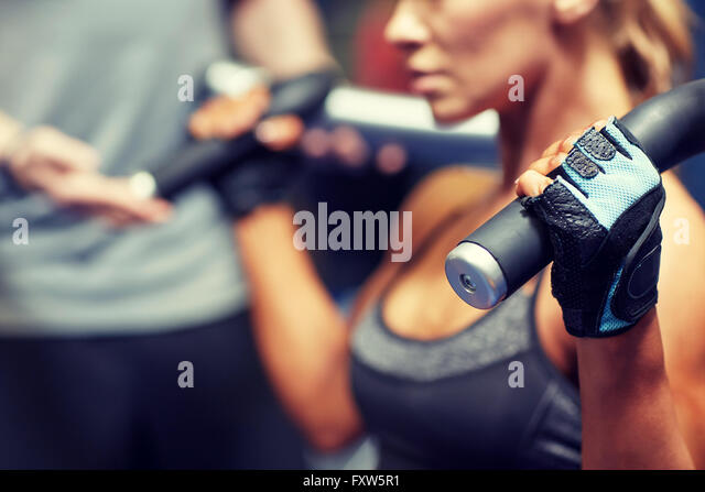man and woman flexing muscles on gym machine - Stock-Bilder