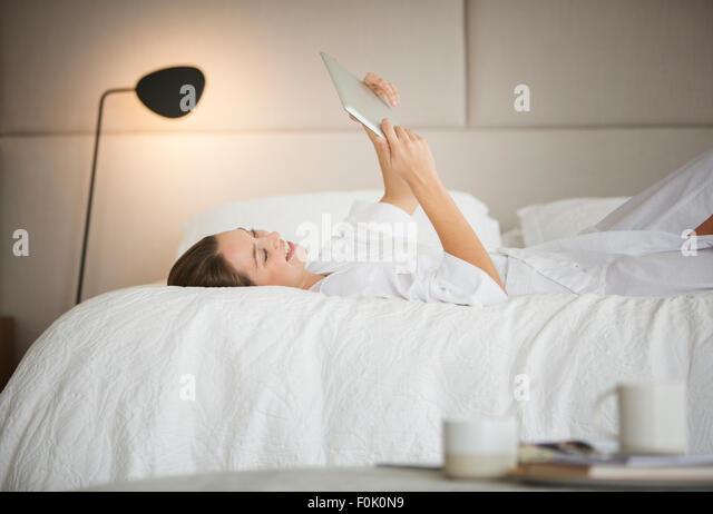 Woman in bathrobe laying on bed using digital tablet - Stock-Bilder