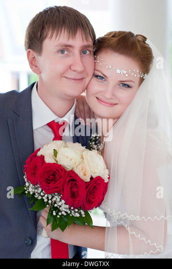beautiful and happy newlyweds stand nearby with each other - Stock Image