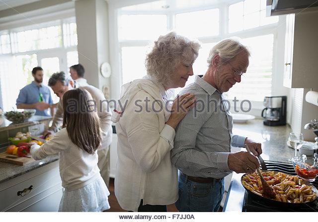 Senior couple cooking at kitchen stove - Stock Image