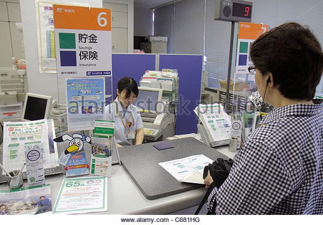 Japan Tokyo Shinjuku post office counter clerk Asian woman customer kanji hiragana katakana characters symbols Japanese - Stock Image