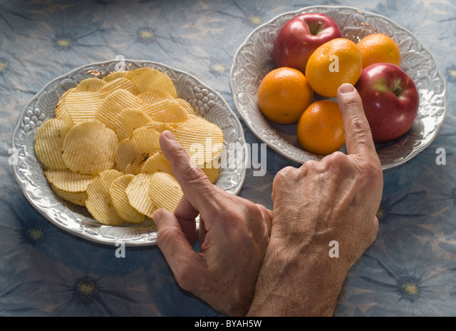 man pointing to bowls of potato chips and fruit - Stock Image