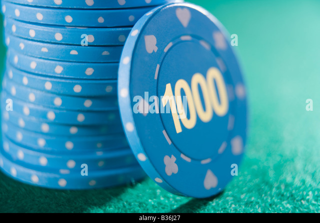 Poker chips piled on a poker table with one thousand chip showing (close up/selective focus) - Stock Image