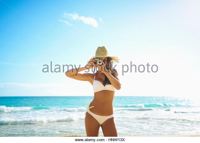 Pacific Islander woman on beach photographing with camera - Stock-Bilder