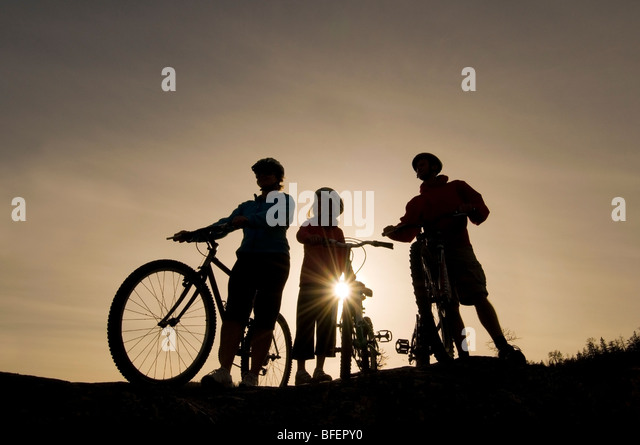 Silhouette of a family taking in the view over Kamloops Lake while mountain biking, west of Kamloops, British Columbia, - Stock-Bilder