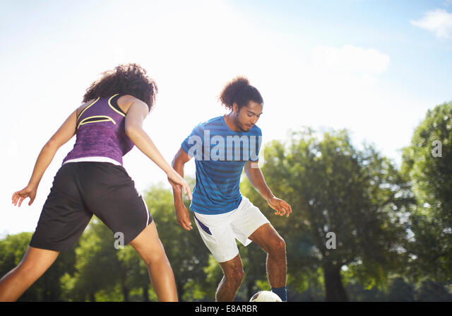 Young couple playing soccer in park - Stock Image