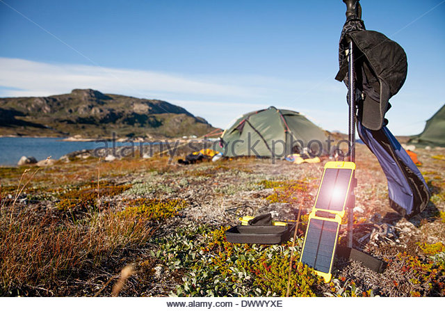 Solar charger with tent in background at campsite - Stock Image