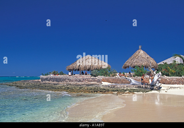 Anguilla beach Scilly Cay thatch unbrellas for swimmers - Stock Image
