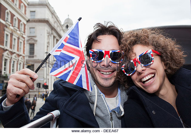 Portrait of exuberant couple with British flag and sunglasses riding double decker bus - Stock Image