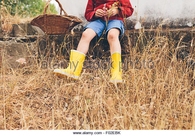 Low section of a boy sitting on a step - Stock Image