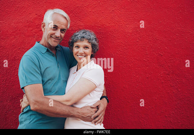 Portrait of loving middle aged man and woman standing together against red background. Senior couple embracing against - Stock Image