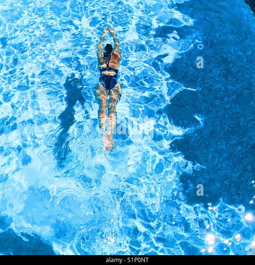 Woman swimming in outdoor swimming pool on a sunny day. - Stock Image