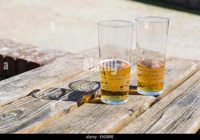 Two half empty glasses of beer or shandy on a wooden pub table, glasses marked Seafarer's Ale - Stock Image