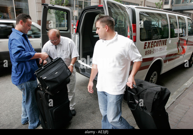 Ohio Cincinnati Hilton Netherland Plaza Hotel airport shuttle van male travelers luggage - Stock Image