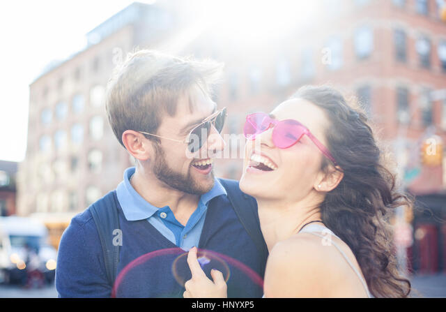 Couple laughing together outdoors - Stock Image