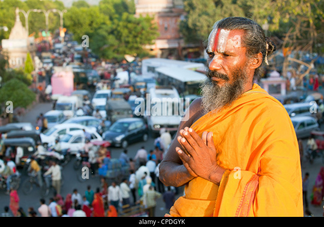 Holy Sadhu meditating high above traffic congestion and street life in the city of Jaipur, Rajasthan, India, Asia - Stock Image