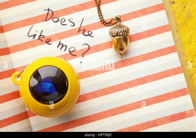 Young girl diary love question and a magic ball toy answering yes. Relationship doubts  and romantic feelings text - Stock Image