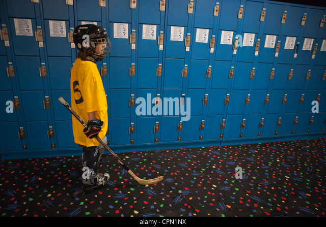 Nine year old boy dressed for roller hockey standing in front of a wall of blue lockers. - Stock Image