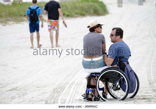 Miami Beach Florida public beach wheelchair disabled man woman - Stock Image