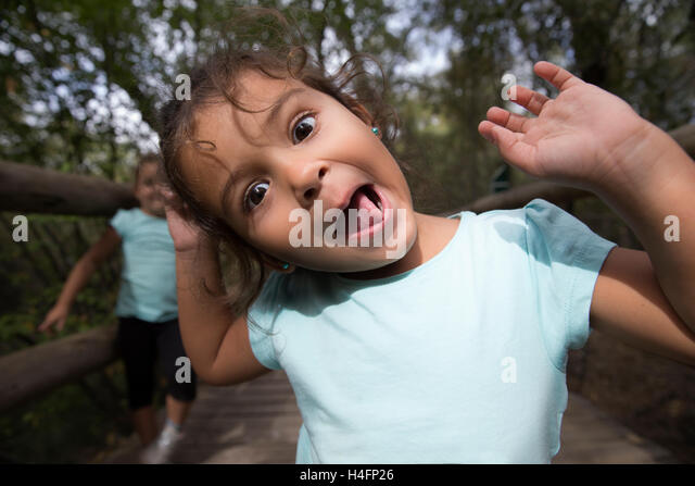 Portrait of cheerful little girl gesturing and making funny grimace at camera in park. Her sister on background. - Stock Image