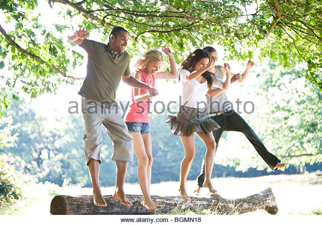 Four young people jumping from a log - Stock-Bilder