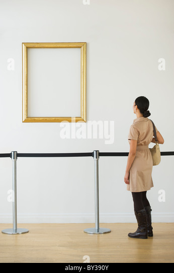 Woman looking at blank picture frame in art gallery - Stock Image