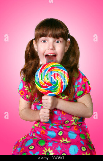 Bright Pink Image of a Girl Licking a Lollipop on Pink Background - Stock Image