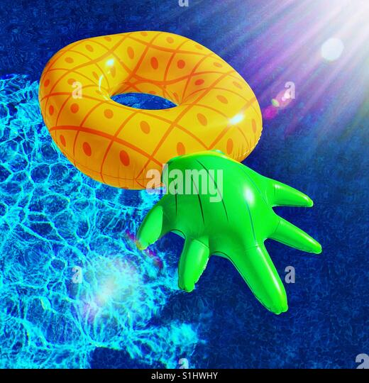 Inflatable pineapple floatie on clear blue waters on a sunny hot day. - Stock Image
