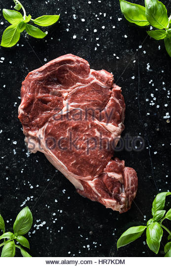 Fresh steak with spices, tomatoes and leafs of basil on marble background. Uncooked beefsteak cooking on a kitchen. - Stock Image